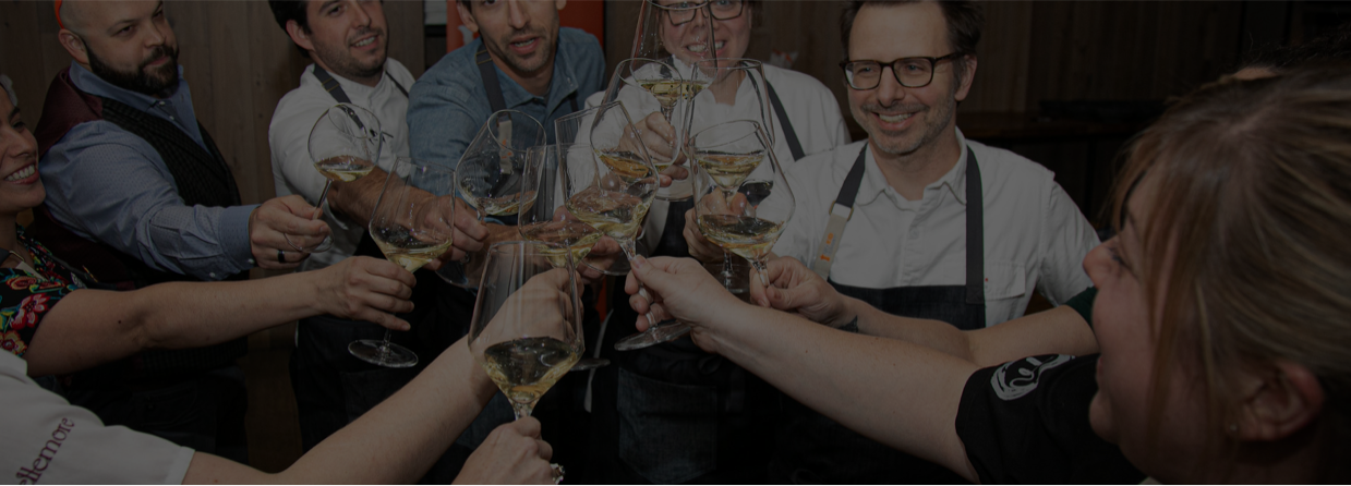 A group of chefs cheers'ing each other over a glass of white wine.