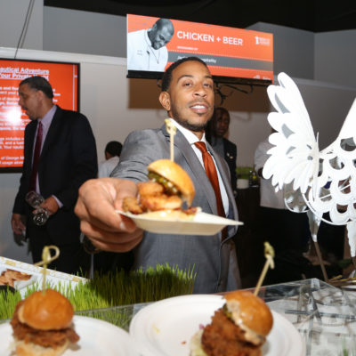 Ludacris holding a tiny plate of a burger